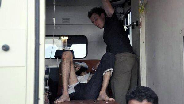 Абдул-Рахман Кэссиг, захваченный боевиками ИГ, оказывает первую помощь раненому. Сирия, август 2013