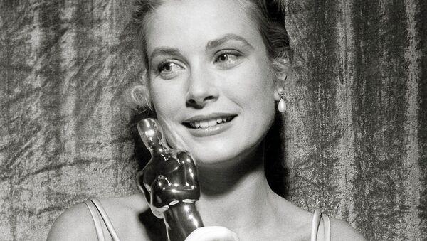 Грейс Келли держит свою премию Оскар за роль в фильме Деревенская девушка