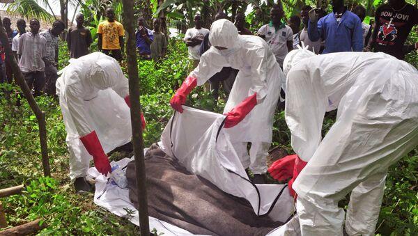 Сотрудники крематория эвакуируют тело человека, предположительно погибшего от вируса Эболы в Либерии