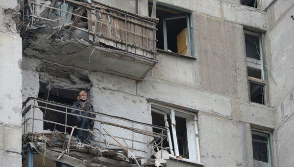 Женщина на балконе дома подвергшегося обстрелу украинскими военными. Архивное фото