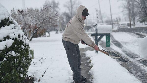 Мужчина очищает дорожку от снега в штате Пенсильвания, США. Архивное фото