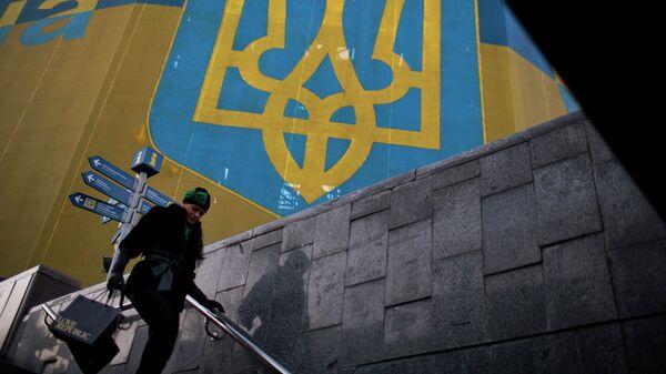 Женщина проходит мимо огромного украинского флага в центре Киева, архивное фото