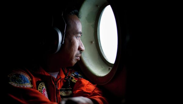 Член экипажа самолета ВВС Индонезии во время поисков пропавшего самолета компании Air Asia
