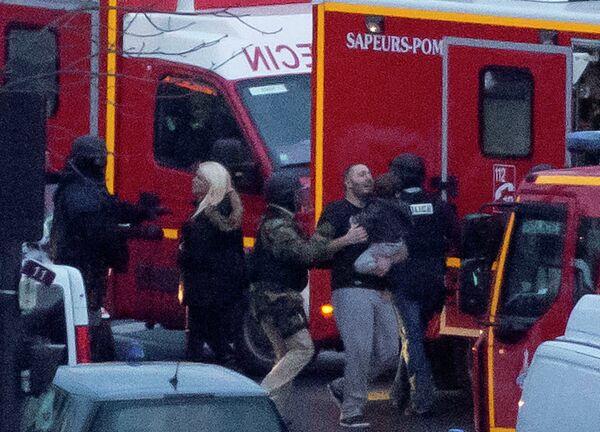 Сотрудник службы безопасности направляет освобожденных заложников после того как они ворвались кошерный рыно