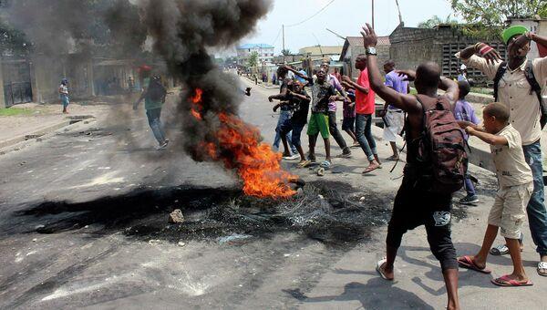 Демонстранты жгут шины на улице в Киншасе, Конго. 21 января 2015