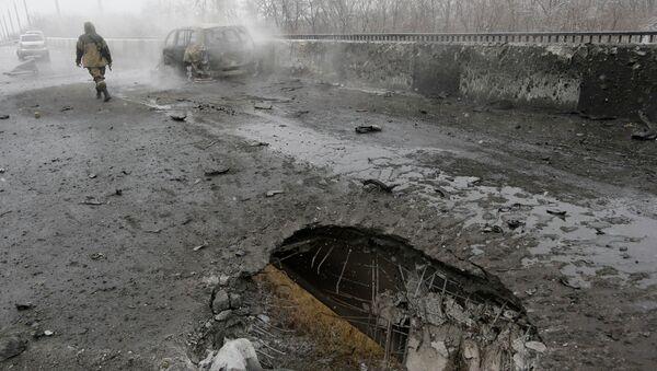 Место попадания снаряда и сгоревший автомобиль в Донецке после обстрела украинскими силовиками. Архивное фото