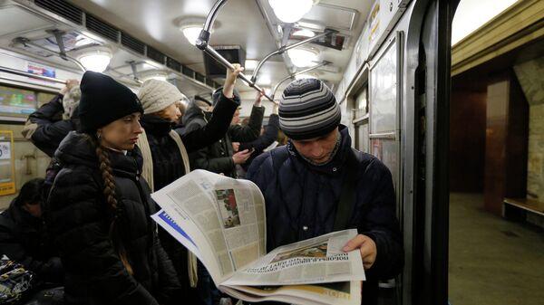 Молодой человек читает газету в метро, архивное фото