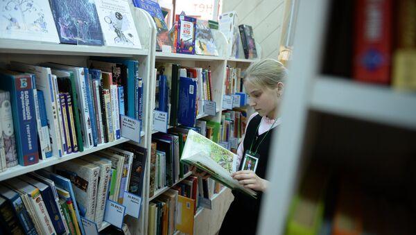 Девочка читает книгу в библиотеке. Архивное фото