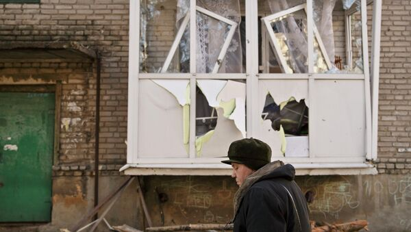 Женщина идет возле поврежденного дома в Дебальцево. Архивное фото