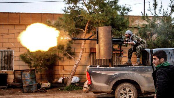 Курдский боец стреляет из зенитной установки по позициям боевиков ИГИЛ в районе Тель-Тамр