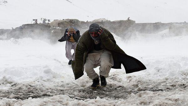 Жертвы лавины бегут навстречу армейскому вертолету для получения помощи. Провинция Панджшер, Афганистан