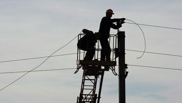 Рабочие восстанавливают линию электропередач. Архивное фото