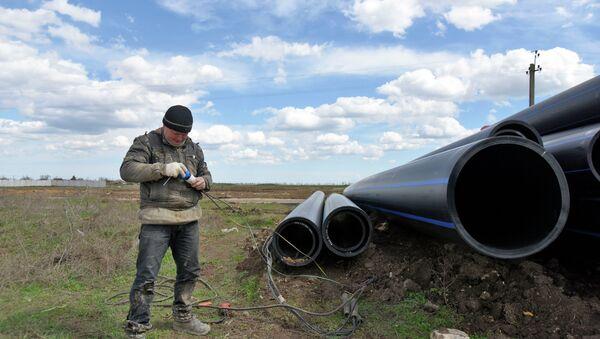 Рабочий выполняет работы по прокладке трубопровода от Северо-Крымского канала. Архивное фото