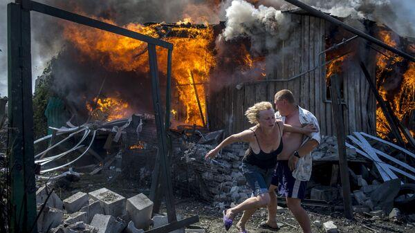 Местные жители спасаются от пожара, возникшего в результате авиационного удара вооруженных сил Украины по станице Луганская, 2 июля 2014. Архивное фото