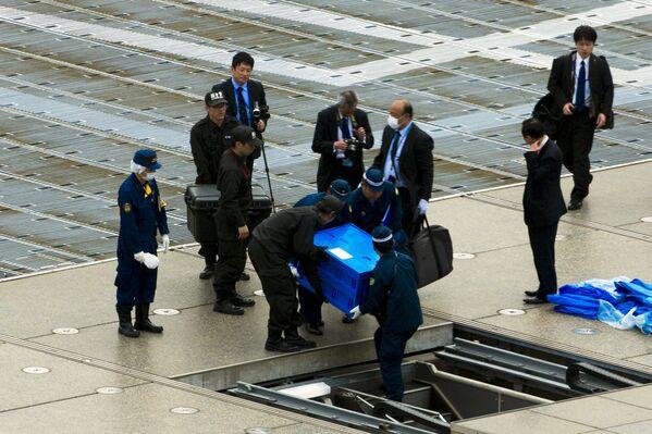 Полицейские выносят ящик с беспиолотником с крыши резиденции премьер-министра Японии Синдзо Абэ в Токио