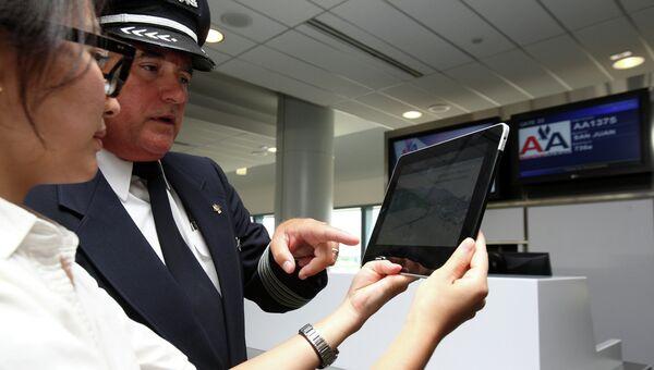 Пилот American Airlines смотрит траекторию полета на ipad. Архивное фото