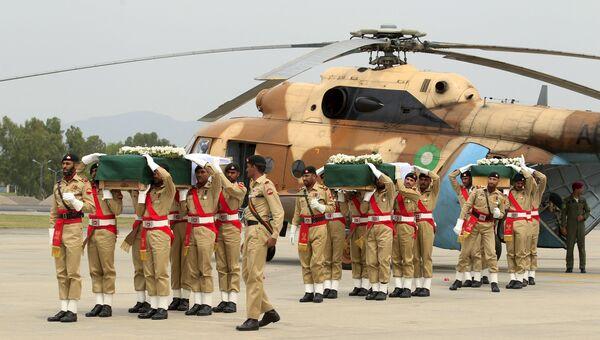 Пакистанские солдаты переносят погибших при крушении вертолета