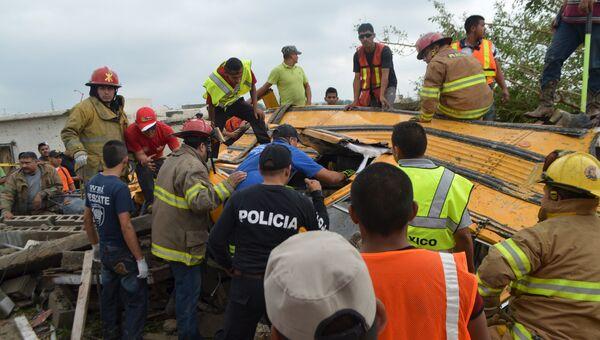 Полиция и пожарные осматривают обломки школьного автобуса после торнадо в Мексике