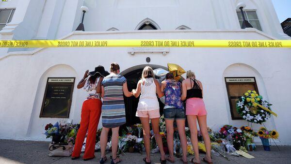 Люди, пришедшие почтить память погибших во время стрельбы в африканской методистской епископальной церкви Эмануэль в городе Чарлстон, США
