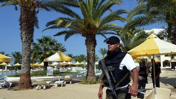 Сотрудник полиции на пляже отеля курорта Эль-Кантауи в Тунисе