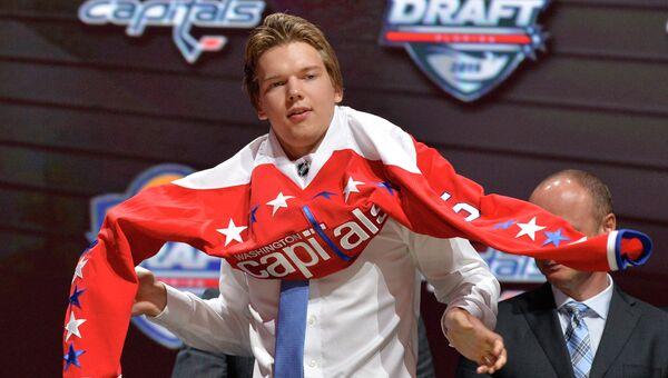 Хоккеист Илья Самсонов надевает свитер команды Вашингтон Кэпиталз