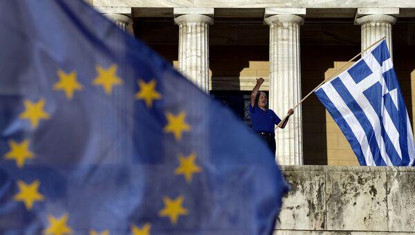 Мужчина держит флаг Греции во время проевропейской демонстрации в Афинах