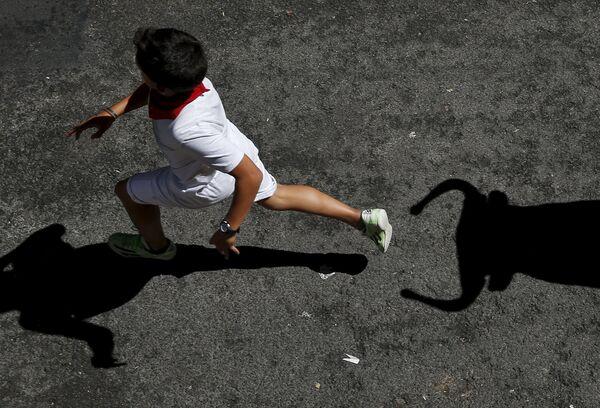 Мальчик убегает от игрушечного быка во время фестиваля Сан-Фермин в Памплоне. Испания, июль 2015