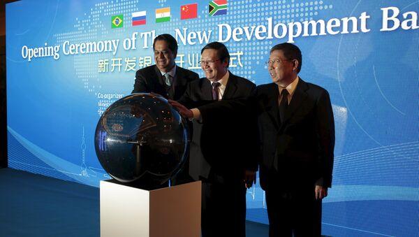 Президент Нового банка развития БРИКС Кундапур Ваман Каматх, министр финансов Китая Лоу Цзивэй и мэр Шанхая Ян Сюн на церемонии открытия нового банка развития в Шанхае