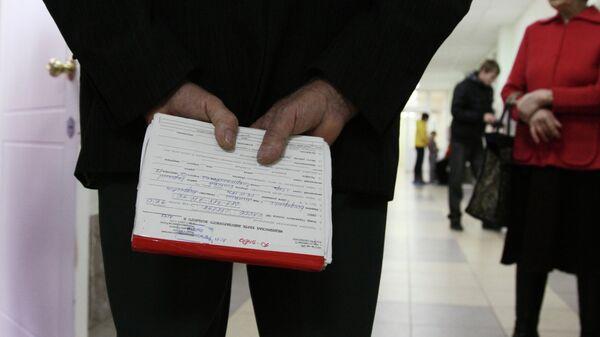 Пожилой мужчина держит в руках медицинскую карточку