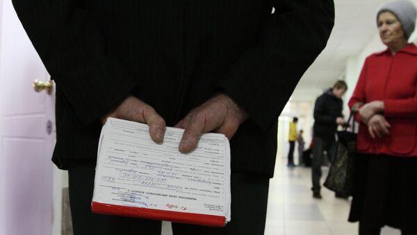 Мужчина держит в руках медицинскую карту. Архивное фото