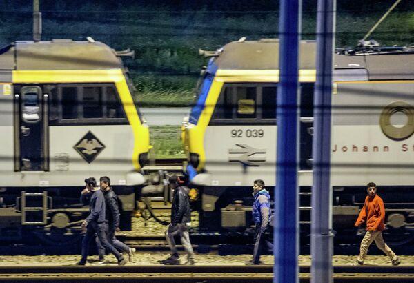 Мигранты идут вдоль железнодорожных путей в терминале Евротуннеля