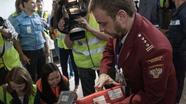 Сотрудник Роспотребнадзора демонстрирует санкционные продукты, подлежащие уничтожению