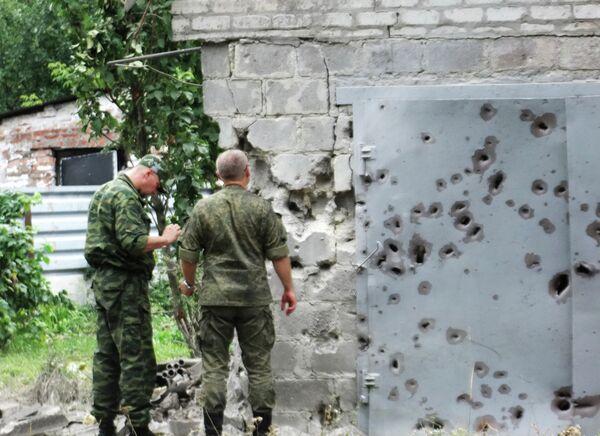 Сотрудники МЧС у ворот, поврежденных осколками в результате обстрела Донецка
