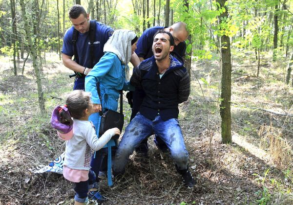 Венгерские полицейские задерживают семью сирийских беженцев после их незаконного пересечения границы с Сербией