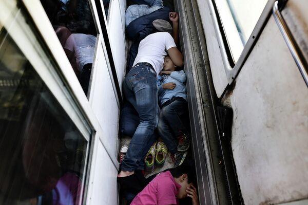 Беженцы из Сирии спят на полу поезда из Македонии в Сербию. 30 августа 2015