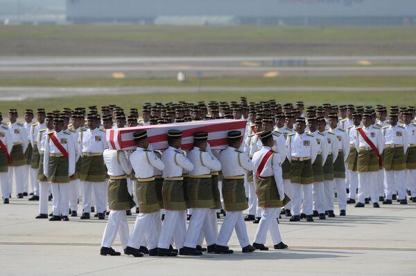 Военные несут гроб с останками жертвы крушения малайзийского самолета Boeing 777 в Донецкой области. Куала-Лумпур