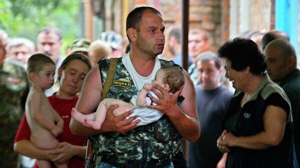 Боец спецназа несет спасенного ребенка во время штурма захваченной боевиками школы в Беслане. 2004 год