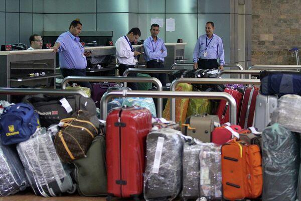 Сотрудники аэропорта курорта Шарм-эш-Шейх с багажом в терминале вылета, Египет. Ноябрь 2015