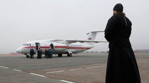 Священнослужитель наблюдает в аэропорту Пулково в Санкт-Петербурге за самолетом МЧС России, доставившим тела жертв крушения Airbus A321 авиакомпании Когалымавиа