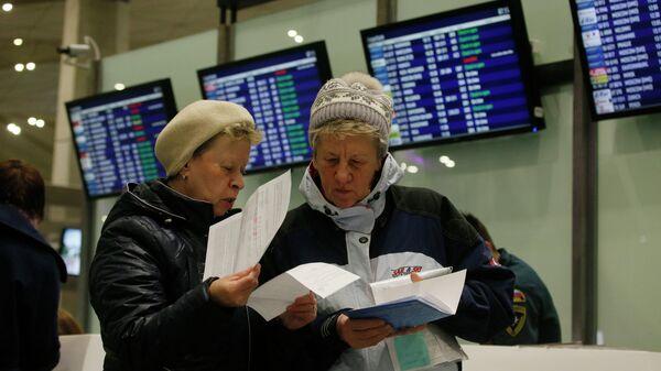Пассажиры проверяют свои документы после возврата билетов до Египта. Аэропорт Пулково, Санкт-Петербург