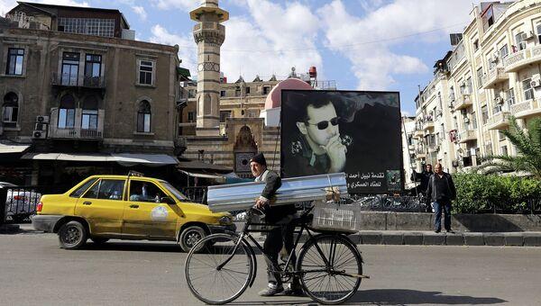 Житель Сирии на улице Дамаска в Сирии на фоне баннера с изображением президента Сирии Башара Асада. Ноябрь 2010