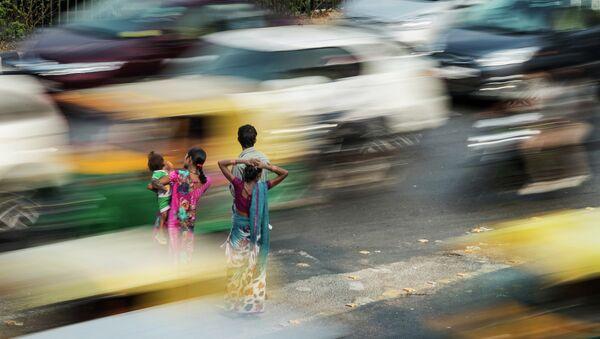Люди стоят на разделительной полосе в час пик в Нью-Дели. Архивное фото