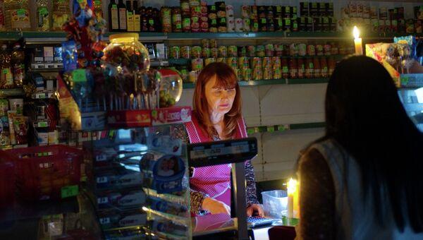 Продавщица торгует при свечах в магазине в селе Чистенькое недалеко от Симферополя. Ноябрь 2015