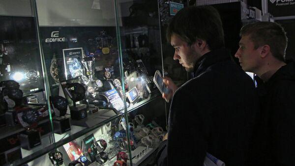Покупатели в одном из магазинов Симферополя рассматривают товары подсвечивая их мобильным телефоном