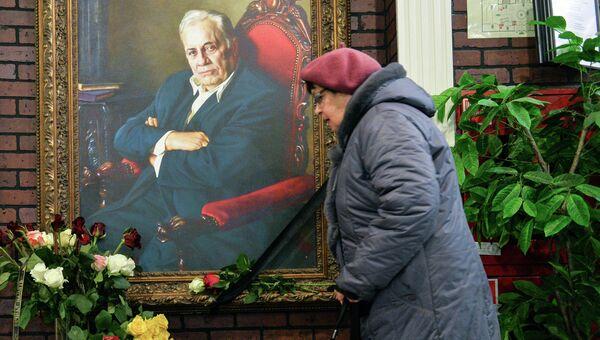 Женщина возлагает цветы к портрету народного артиста СССР режиссера Эльдара Рязанова