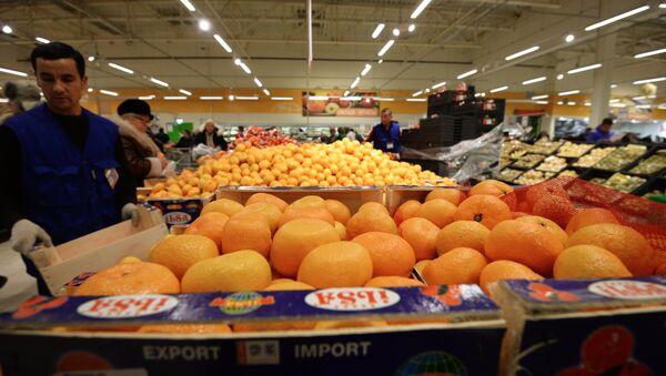 Продавец у прилавка с мандаринами из Турции в торговом зале гипермаркета Глобус. Архивное фото