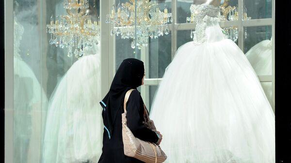 Женщина проходит мимо витрины магазина со свадебными платьями в Саудовской Аравии