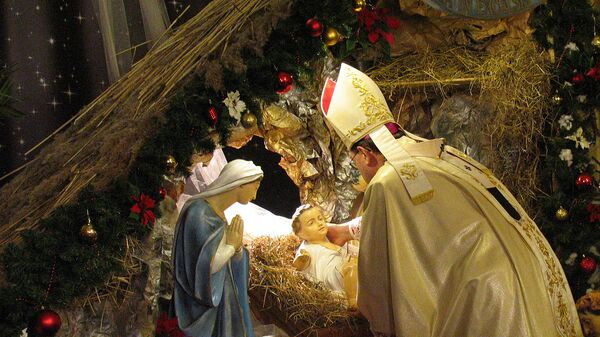 Архиепископ Павел Пецци возлагает фигурку младенца Иисуса в ясли в московском кафедральном соборе