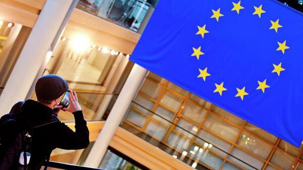 Турист фотографирует флаг Евросоюза