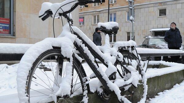 Занесенный снегом велосипед на одной из улиц Варшавы, Польша